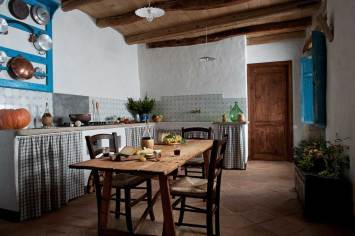 the old kitchen with some wine and cheese on the table