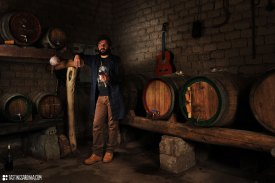 a vernaccia wine producer sipping some wine in his own unfired mud-bricks cellar