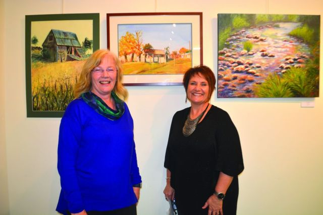 Tumut art Society president Glenyce Francis and Art Experience teacher Jennie Forster with Glenyce's artwork 'Little Cottage.'