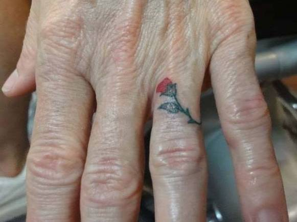 A small tattoo on the finger in an elderly woman - Rose