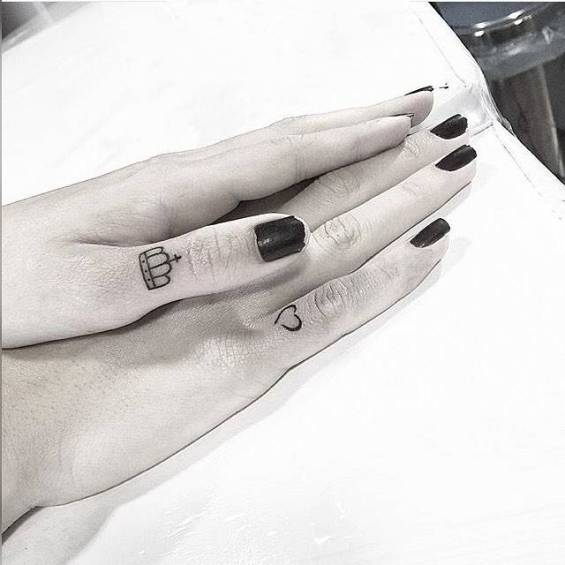 Tattoos on the fingers of the girl - the crown and the heart