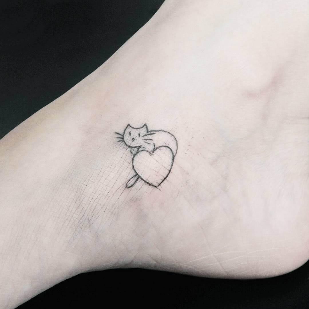 Tattoo Katze auf einem Herzchen