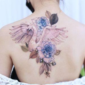 Cisne en vuelo entre flores azules por Chaewha Tattoo