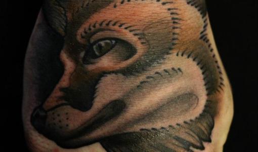 Tatuaje de un lobo en el puño