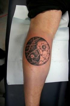 Yin y yang tatuado en la pierna