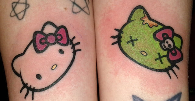 """0f16a5071e71b A pair of Hello Kitty tattoos on the arms of a girl. It is the face of  Japan's cutest cat, and on the other side a """"zombie"""" version of her."""