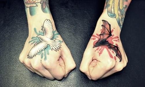 Bat and dove tattoo on fists
