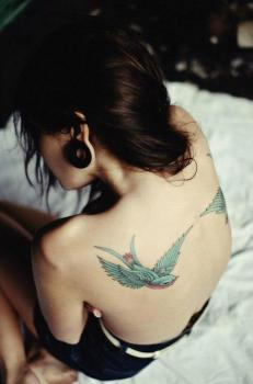 Tatuaje pájaros volando sobre la espalda
