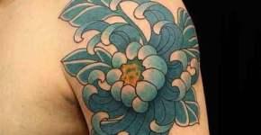 Flor azul tatuada en hombro