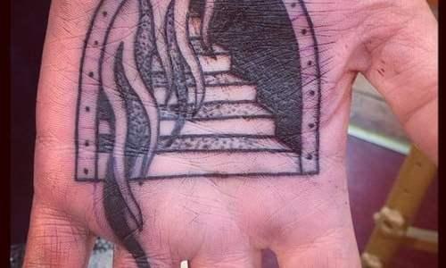 Puerta hacia el infierno tatuada en mano