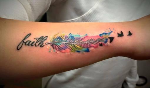 Tatuaje pluma de colores en el brazo