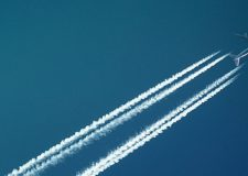 A plane cuts diagonally across a deep blue sky, leaving contrails behind it