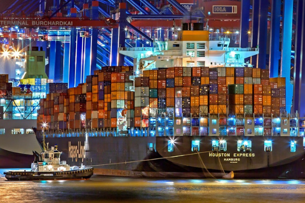 A tugboat pulls a large cargo ship into port