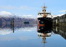 A ship docked in front of a snow capped mountain