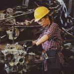 woman engineer working on engine in factory wearing a heard helmet
