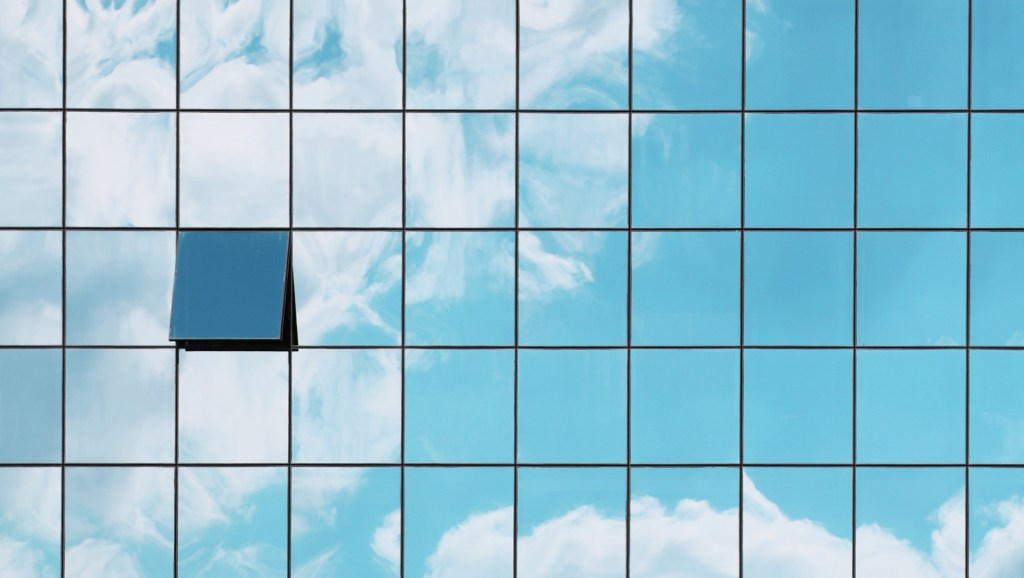 A single open window in a grid of closed glass windows mirroring the sky
