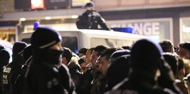 Polizeibeamte und männliche Besucher stehen sich in der Silvesternacht in Köln gegenüber