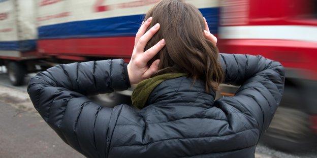 Eine Frau steht an einer Straße und hält sich die Ohren zu.
