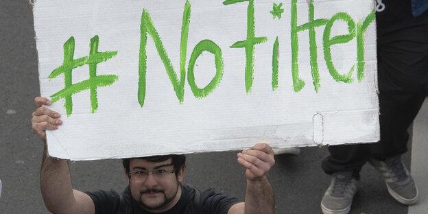 """Ein Mann hält ein Plakat mit der Aufschrift """"No Filter"""" hoch"""