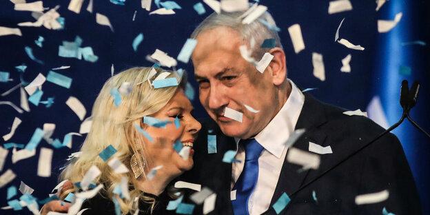 Netanyahu with woman in confetti rain.