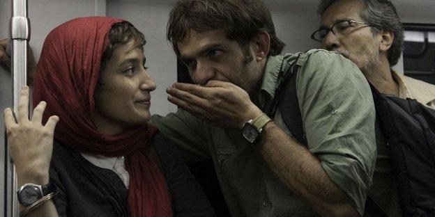 Eine junge Frau mit Kopftuch und ein junger Mann in der Ubahn. Er flüstert ihr etwas zu.