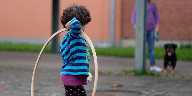 Ein Kind spielt mit einem Reifen