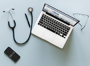 stethoscope laptop and phone to illustrate the risk to health care organizations from phishing emails