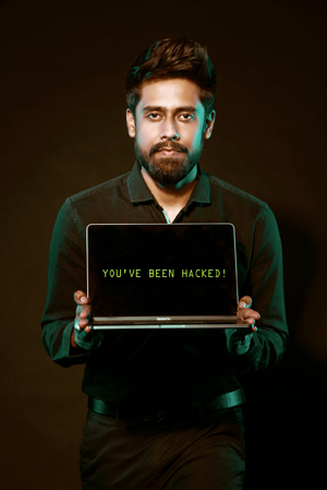 "a frustrated-looking man holds a laptop with the words ""you've been hacked"" on the screen"
