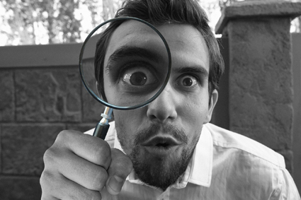 Goofy black and white photo of man with goatee holding up a magnifying glass. The eye behind the glass is exaggerated for comic effect.