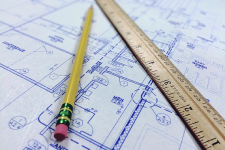 Photograph of pencil and ruler laying on top of a construction blueprint to illustrate how the NIST Cybersecurity Framework provides a guideline to protect your business.