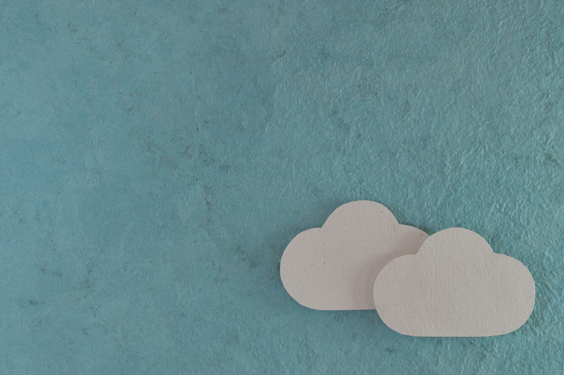 """Two small paper """"clouds"""" float on a sky-blue paper backround"""