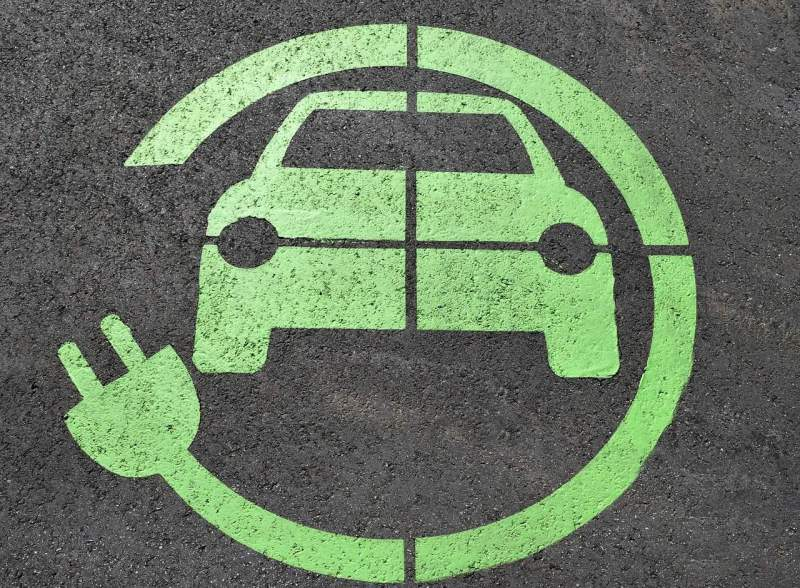 Green icon of a car surrounded by an electrical cord