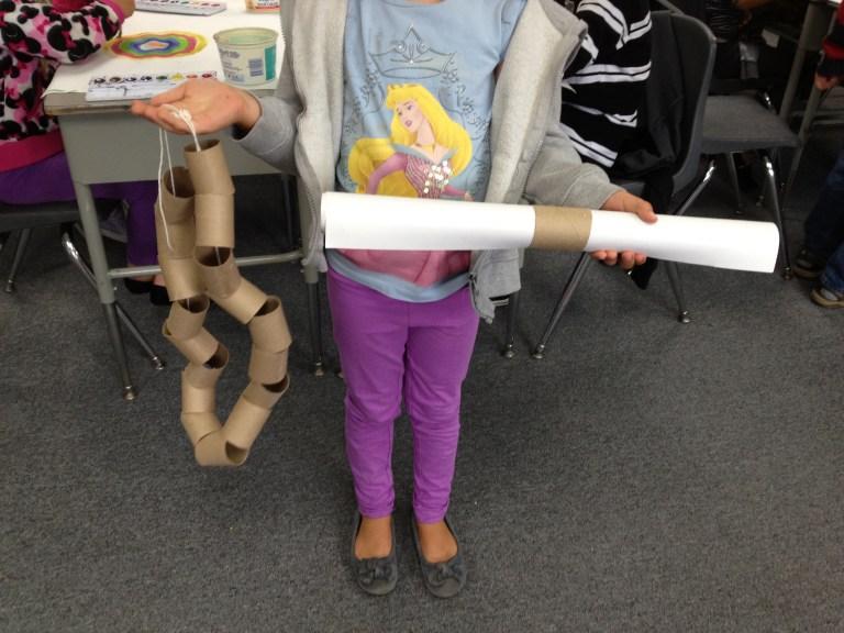 1st grader holding art in a tube
