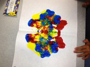 Unfolding paper to reveal a symmetrical Rorschach Print