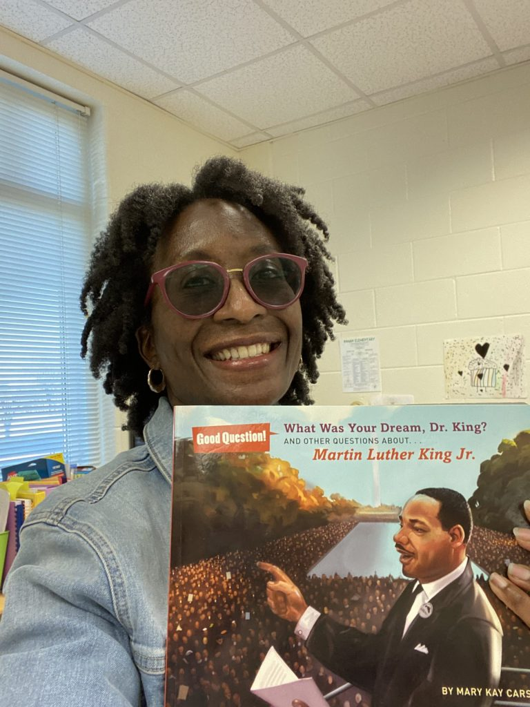 An image of me, an African-American woman wearing red, tinted glasses and a jean jacket. I am holding up a book about Dr. Martin Luther King, Jr.