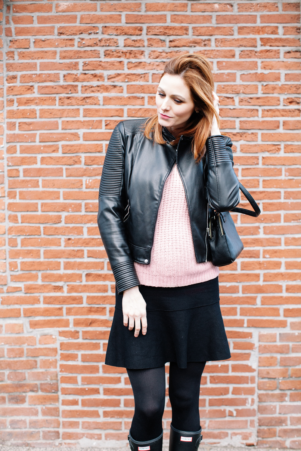 Black leather jacket and light pink sweater