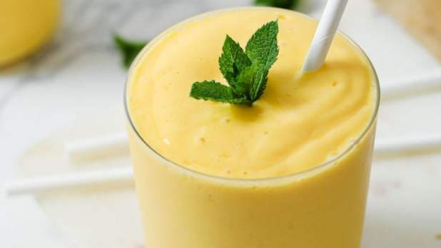 Mango Lassi in a clear glass with white straw