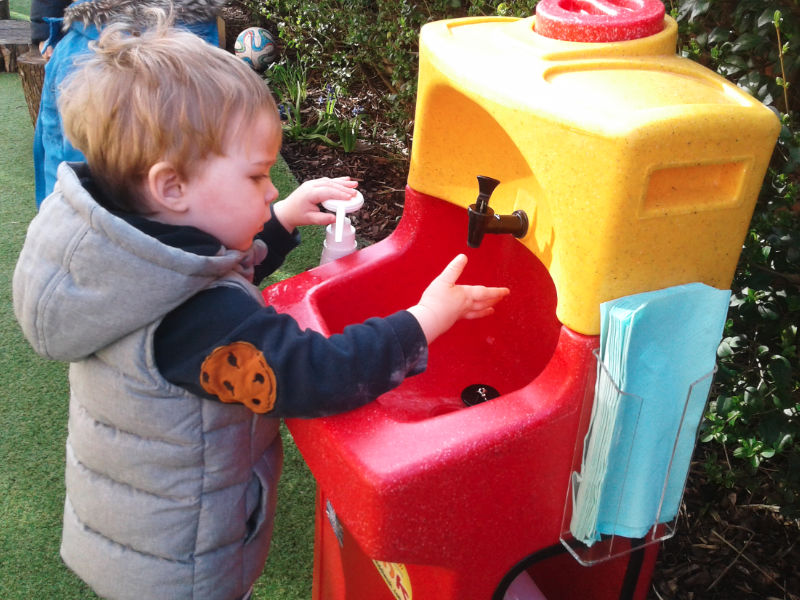 A child soaps his hands before washing with a KiddiSynk portable hand wash unit