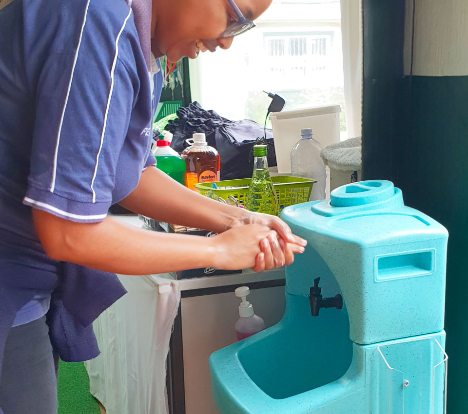 Washing hands in South Africa with a Teal Easywash WashStand