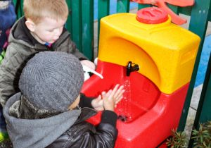 2 children washing their hands outdoors with a portable sink