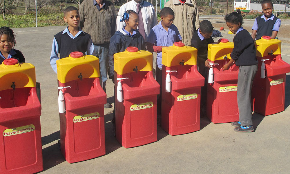 Children learning how to wash their hands properly with Teal KiddiSynk portable units
