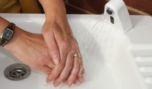 Woman washing hands with a HandSpa portable sink