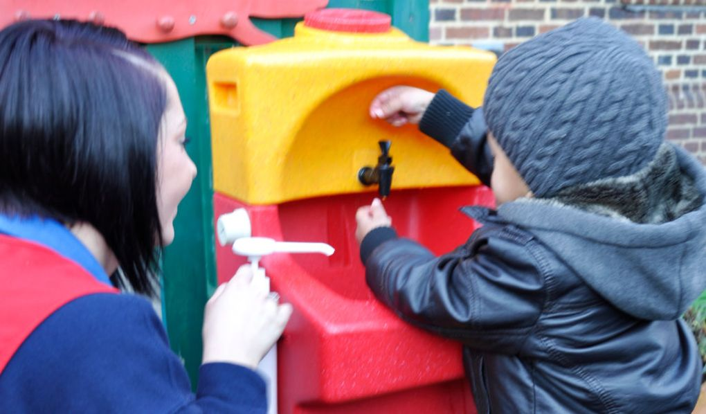 Childcare worker supervises hand washing with Kiddiwash portable sink