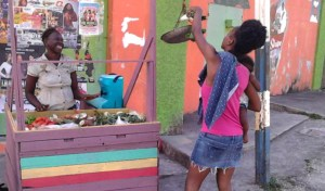 Teal portable hand wash unit being used by street food seller in Jamaica