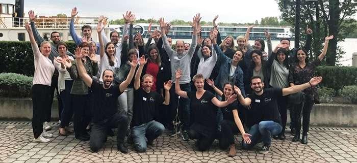 Teamfoto Medtronic Limited bei Teambuilding Event beim Hilton Danube Waterfront an der Donau. Leute jubeln und haben Spaß