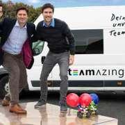 Drei Männer stehen auf Riesenlabyrith. Mario Kart Autos.