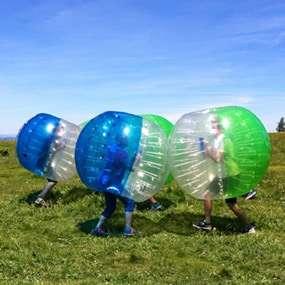 """Auf einer grünen Wiese spielt ein Team als Teambuilding Aufgabe mit Bubbles den Spielmodus """"capture the flag"""""""
