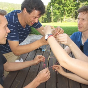 Team versucht als Teambuilding Aufgabe mit Spaghetti, einer Schnur und einem Klebeband einen Turm zu bauen