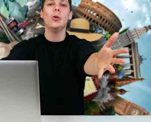 Person vor Laptop mit Welthintergrund zeigt auf Kamera.