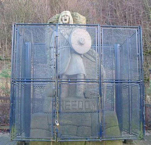 freedoms statue in cage behind fence ironic irony Funny Statues Weird Statues Bizarre Sexual Strange Statues Awkward Crazy Art